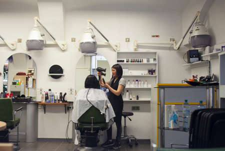 VIENNA, AUSTRIA - MAY, 22: Hairdresser drying hair with drier, makes hairstyle in a hairdressing salon on May 22, 2018 Publikacyjne