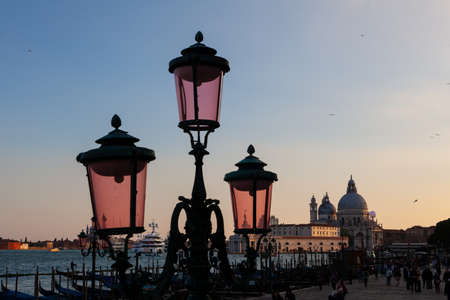 VENICE, ITALY - MAY, 09: View of typical Venetian street lamp, behind the basilica of St. Mary of Health on May 09, 2019