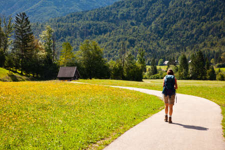 Young woman with backpack hiking along the path in the Slovenian countryside. Bohinj