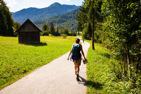 Young woman with backpack hiking along the path in the Slovenian countryside. Bohinj Stockfoto