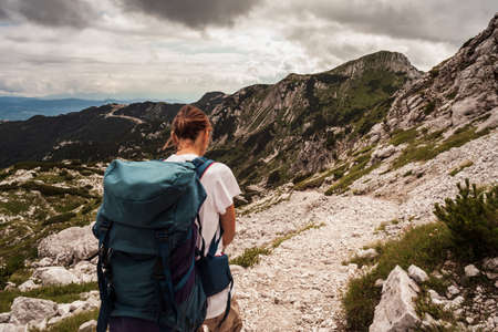 Young woman with backpack hiking along the path in the scenic Vogel mountain part of southern Julian Alps and Triglav National Park heritage of Slovenia