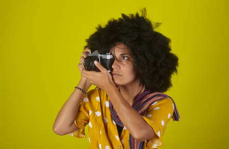 Beautiful indian girl with afro curly hairstyle talking pictures with retro camera on yellow background