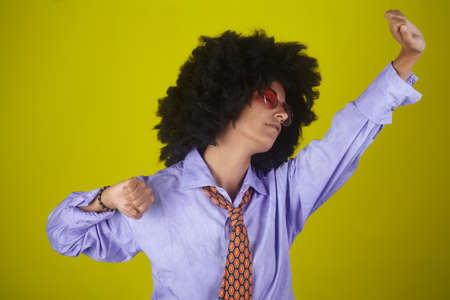 Beautiful indian girl with afro curly hairstyle and male clothes waking up and stretching on yellow background