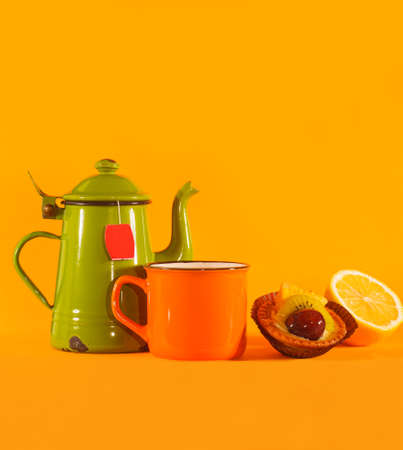 Set of vintage teacup, orange cup, lemon and pastry on orange background. Copy space on top