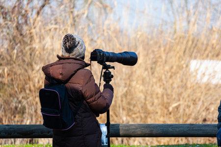 Bird photographer take photos with a camera and telephoto, Laguna di Marano