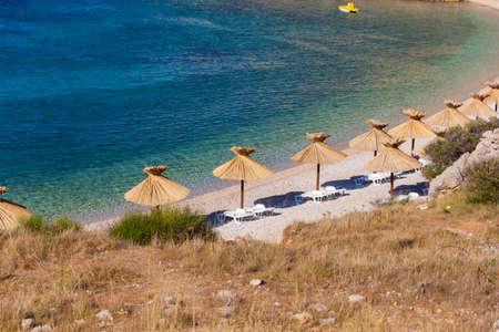 Straw umbrellas in the beautiful Oprna beach in the Krk island, Croatia