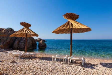 View of the straw umbrellas in the beautiful Oprna beach in the adriatic bay of the Krk island, Croatia