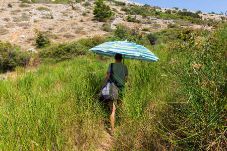 Woman walks along the path grass protecting herself from the sun with a parasol in the Krk island
