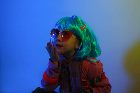 Little girl blowing kiss wearing a colorful wig and heart-shaped sunglasses posed for a photo shooting on the disco light background