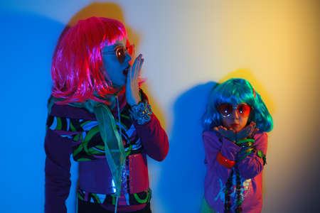 Two little girls blowing kiss wearing a colorful wig and heart-shaped sunglasses posed for a photo shooting on the disco light background