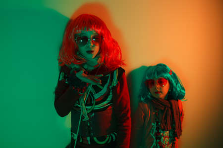 Two little girls wearing a colorful wig and heart-shaped sunglasses posed for a photo shooting on the disco light background