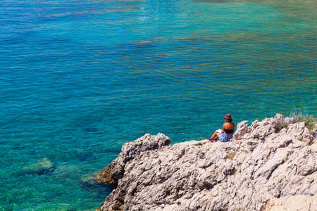 Stara Baska, Croatia - July, 22: Girl reading a book sitting on the rock next to the sea on July 22, 2020 Stok Fotoğraf