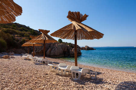 Girl relaxing on the deck chair while reading a book under a straw umbrella in the Oprna beach, Krk island, Croatia Stok Fotoğraf