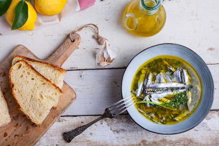 Flat lay of Marinated anchovies in lemon juice with olive oil garlic and parsley. Traditional mediterranean summer food Stok Fotoğraf