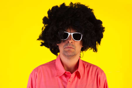 Curly man wearing sunglasses looking at camera on yellow background
