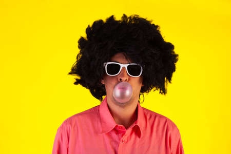 Curly man wearing sunglasses blowing bubble with chewing gum on yellow background