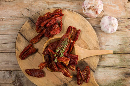 Top view of Mediterranean dried tomatoes garlic, and thyme on wooden table Stok Fotoğraf