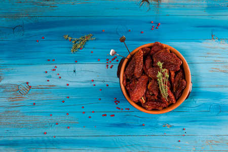 Top view of Mediterranean dried tomatoes inside a bowl on blue rustic wooden