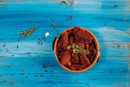 Top view of Mediterranean dried tomatoes and thyme inside a bowl on blue rustic wooden