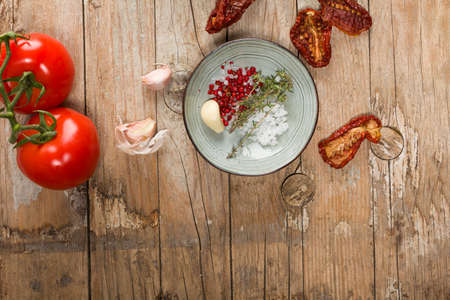 Top view of Mediterranean dried tomatoes, garlic, and fresh tomatoes on wooden table Stok Fotoğraf
