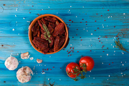 Top view of Mediterranean dried tomatoes inside a bowl, garlic and fresh tomatoes on blue rustic wooden Stok Fotoğraf