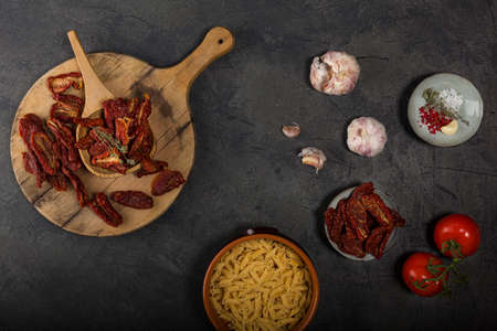 Top view of Mediterranean dried tomatoes garlic, pasta and fresh tomatoes on black Stok Fotoğraf
