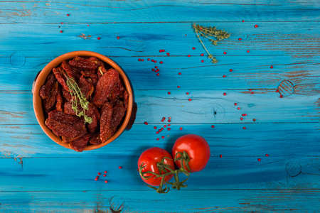 Top view of Mediterranean dried tomatoes inside a bowl and fresh tomatoes on blue rustic wooden Stok Fotoğraf