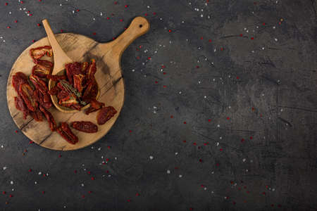 Top view of Mediterranean dried tomatoes on wooden cutting board