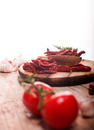 Mediterranean dried tomatoes garlic, thyme and fresh tomatoes on wooden table