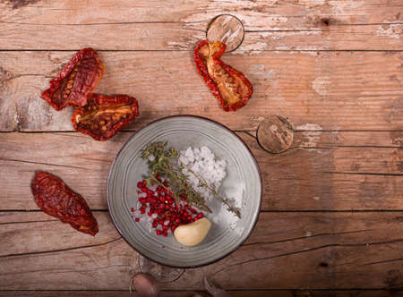 Top view of Mediterranean dried tomatoes, garlic, and spices on wooden table Stok Fotoğraf