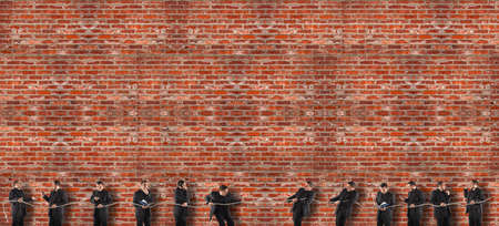 Team competing in tug of war. While some strive and do their duty, others are inattentive and delegate the work to others. Background of red bricks wall