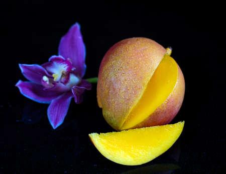 Close-up studio shot mango fruit with slice and leaf isolated on black background