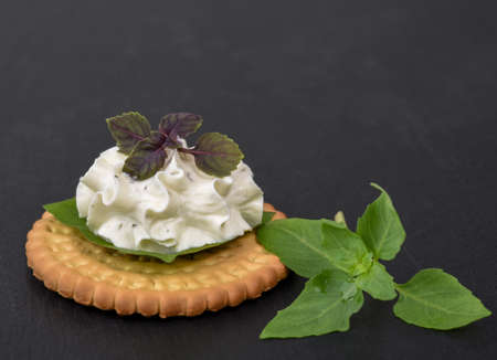 Biscuit cracker appetizer with cream cheese and basil topping on black stone background
