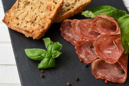 Salami smoked sausage slices basil leaves, peppercorns and bread toast on black stone background
