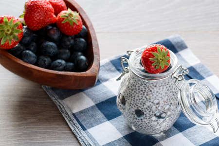 Chia seed pudding with berries in glass jar, wood bowl with berrys