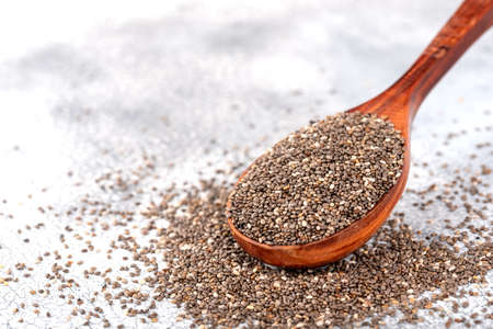 Healthy Chia seeds in a wooden spoon on the table close-up