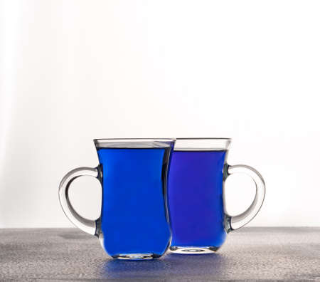 Cups of butterfly pea tea isolated on white background.