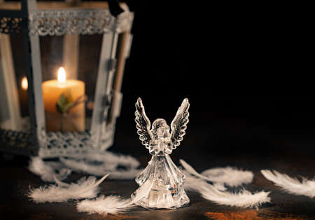 Glass angel with fallen feathers and candle on a dark background