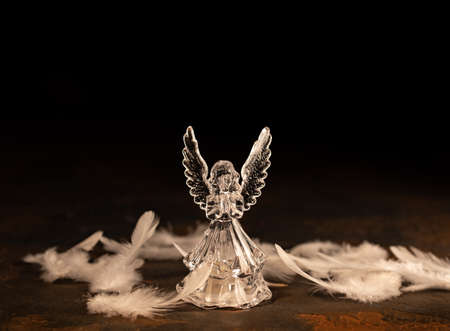 Glass angel with fallen feathers on a dark background 免版税图像