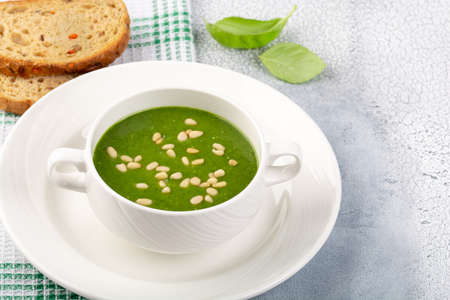 The concept of a healthy, vegetarian or dietary food: cream spinach soup, with pine nuts and basil. With slices of vegetarian carrot bread. On a light background.
