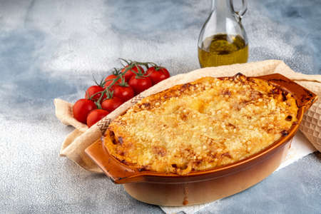 Traditional italian cannelloni with vegetables, minced meat and cheese. On a wooden background. Top view, copy space. Foto de archivo - 129780855
