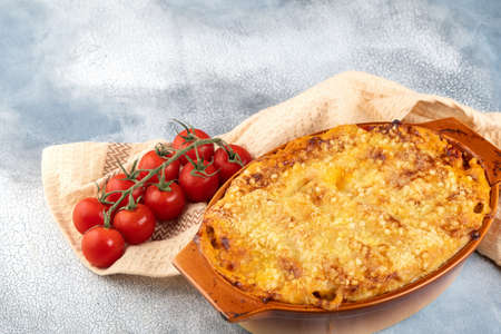 Traditional italian cannelloni with vegetables, minced meat and cheese. On a wooden background. Top view, copy space. Foto de archivo - 129780857