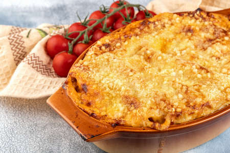 Traditional italian cannelloni with vegetables, minced meat and cheese. On a wooden background. Top view, copy space. Foto de archivo - 129780863
