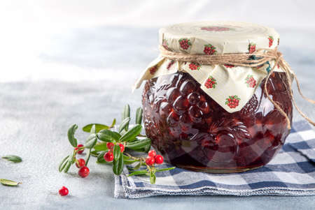 Lingonberry jam in a glass jar with a spoon and cranberries, cowberries on light background. Copy space 写真素材