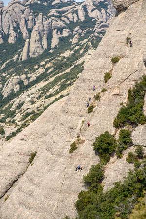 climbers climb to the top of a cliff near Montserrat monastery, Barcelona, Catalonia, Spain Stock fotó