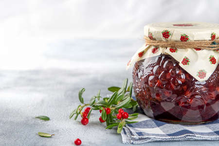 Lingonberry jam in a glass jar with cranberries, cowberries on light background. Copy space Stock Photo