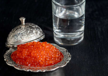 Red caviar in silver bowl with Russian vodka on black background.