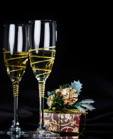 Greeting card: Christmas and New Year concept. glasses of champagne, fir branches with gift box on a dark background.