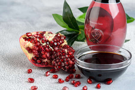 Glass bottle and saucer of pomegranate sour sauce with fresh ripe pomegranate fruits with resolution on a light rustic background.