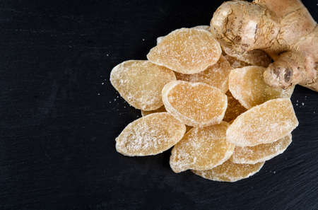 Sweet and Spicy Candied Ginger in a Bowl on black background. Copy space Standard-Bild
